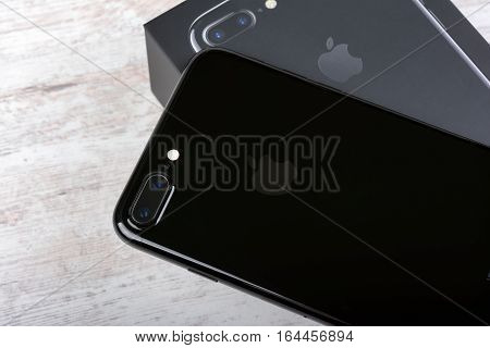 BURGAS, BULGARIA - DECEMBER 29, 2016: New Apple iPhone 7 Plus Jet Black, back side, on white wooden background.