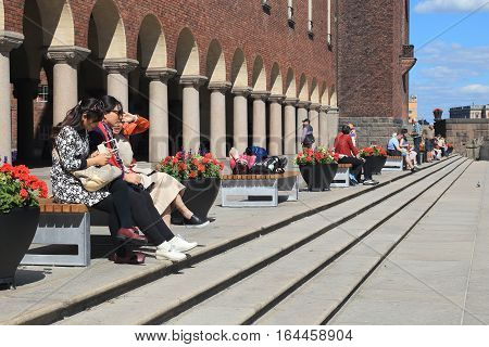 STOCKHOLM, SWEDEN - JUNE 27, 2016: People rest near Venetian-style colonnade that divides the City Hall from the terrace with a public garden at Lake Malaren.