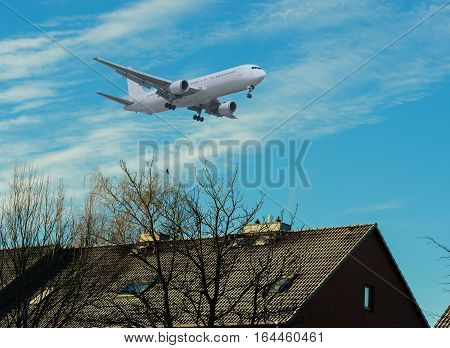 Airplane in landing approach over a residential area