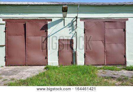 Two brown door and a door in the wall.