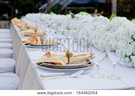 Table set for wedding or event party. Elegant and luxury decoration in soft orange with flowers silver cutlery wine glasses textile napkin.