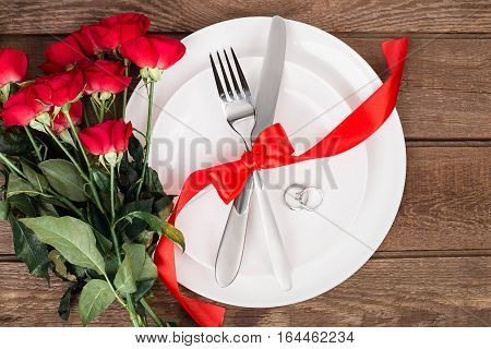 Top view closeup of romantic dinner serving with a bouquet of red roses and ring above the white plate. Still life