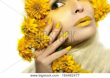 Yellow makeup and manicure with a sharp oval shape of the nails on the girl with the flowers.