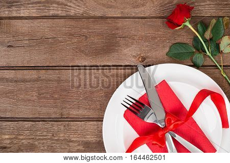 Valentines day table setting with plate, fork, knife, ribbon and rose. Valentines day background. Still life