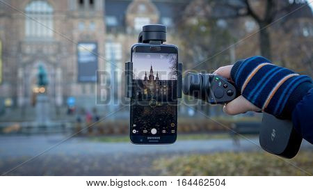 Stockholm, Sweden - October 28, 2016: DJI Osmo Mobile gimbal device with Android Samsung phone