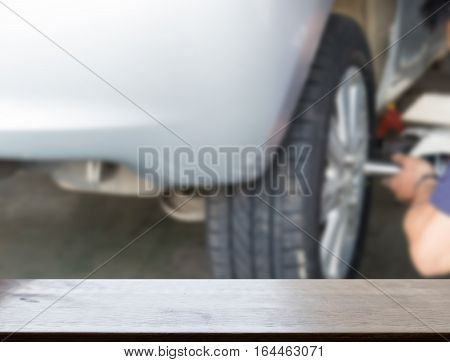 Auto Mechanic In His Workshop Changing Tires Or Rims (blur Image) With Selected Focus Empty Wood Tab