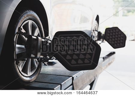 Car on stand with sensors on wheels for wheels alignment camber check in workshop of Service station
