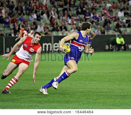 MELBOURNE - SEPTEMBER 12: Will minson burns off Darren Jolly in the AFL second semi final - Western Bulldogs vs Sydney Swans, September 2008