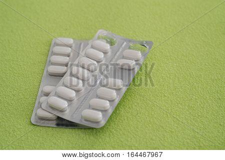 Blister pack of white medicine pills on green background