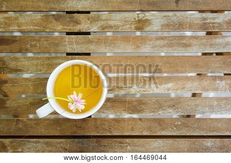 A cup of tea with falling flowers on wooden table in the garden