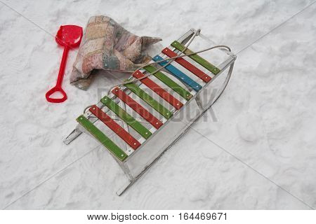 Winter snow. Retro sled made of aluminum, Children red shovel, blanket for toboggans. By Sledge tied rope. On the snow traces of the legs.