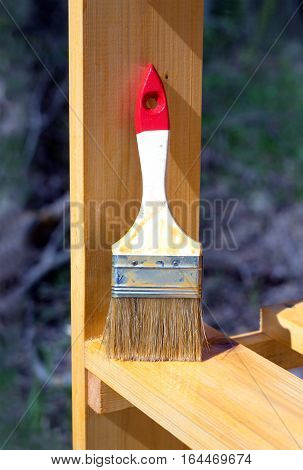 Work over. Paintbrush stands vertical on a painted wooden shelving surface. Photo closeup