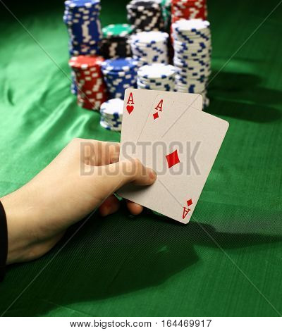 male hand holding two aces. Poker in the casino.