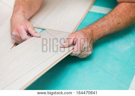 Handyman laying down laminate flooring boards while renovating a house.