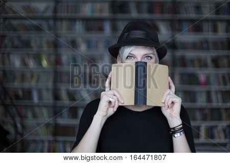 Portrait of woman in black hat with opened book face half-covered white hair. Hipster student girl in a library