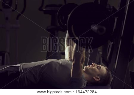 Young muscular built man lying on the bench and lifting a barbell at the gym