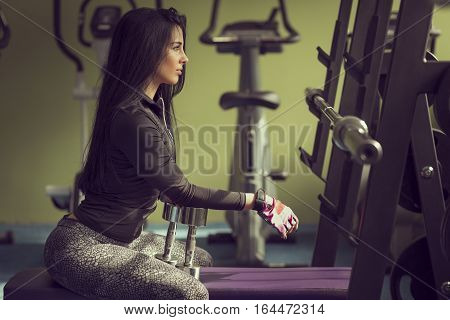 Attractive muscular young woman taking a break on workout in the gym sitting on a bench