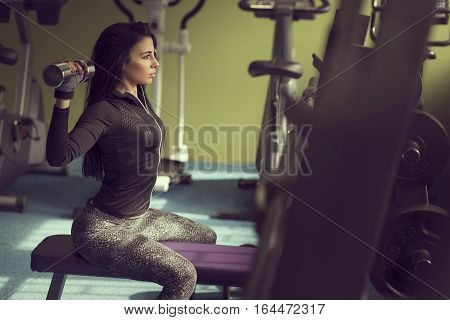 Attractive muscular young woman sitting on a bench working out in a gym lifting weights