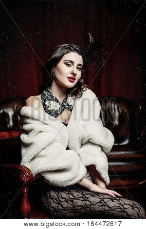 beautiful woman in evening cloth sitting in  victorian chair