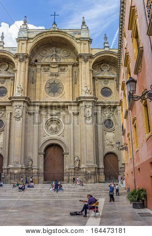 GRANADA, SPAIN - MAY 14, 2013: Central square with tourists, a misician and the Cathedral in Granada, Spain
