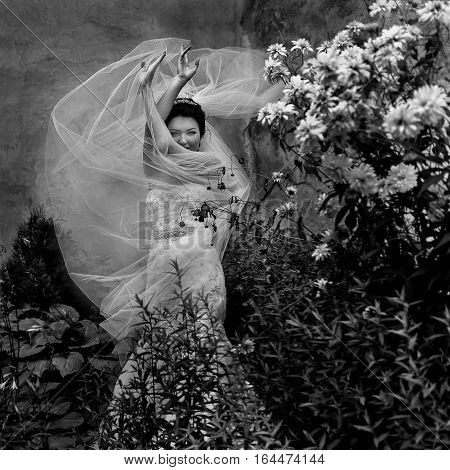 Veil Flies Up To The Delicate Bride's Hands While She Stands In The Garden