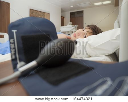 A young female patient looking to camera from a hospital bed through a blood pressure monitor.