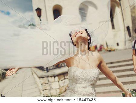 Bride's Veil Flies Up While She Walks Around A City