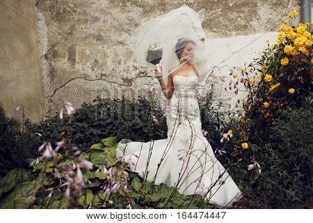 Wind Blows Bride's Veil To An Old Wall While She Stands Among The Flowers