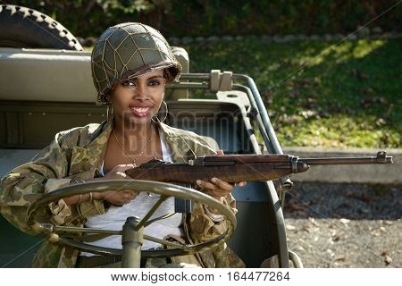 pretty young woman with ww2 a camouflage uniform and helmet