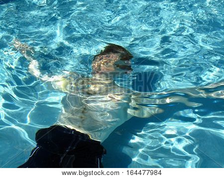 man swimming in a swimming pool underwater