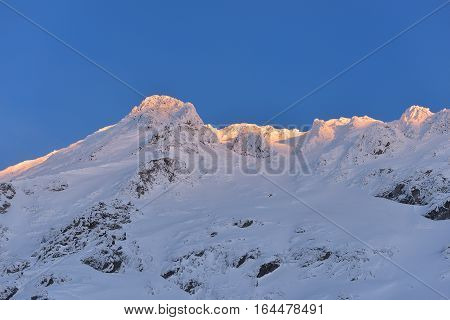 Beautiful view of mountain peak with sunset light on top against clear blue sky