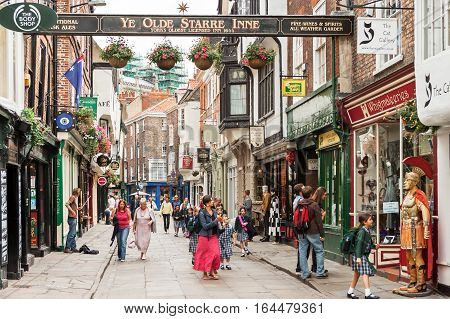 York Yorkshire United Kingdom - June 23 2006: A view of the Stonegate street. It is one of the oldest streets in York with some of the half-timbered buildings. Tourists visiting and shopping in York's popular Stonegate shopping street.