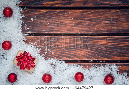 Winter holiday background. Baubles gift and snow on a wooden boards.