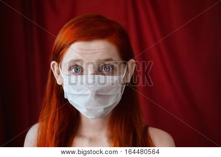 red-haired girl with a medical mask on a red background woman doctor woman with intense look European appearance facial wrinkles on the forehead eared girl