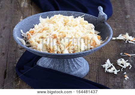 Homemade Sauerkraut with carrots in an elegant stone plate with a bird on a rough wooden background with dark blue cloth. On the table is scattered sauerkraut.