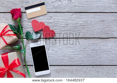 Valentine day internet sales concept, online shopping holiday background with copy space. Mobile phone on rustic wood with rose flower, hearts and credit card, top view. Card and advertising mockup