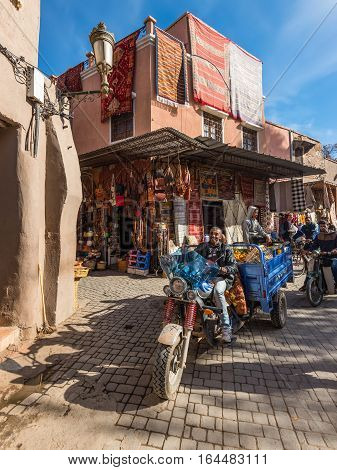 Marrakesh Morocco - December 8 2016: People transport and shops in the famous souks of Marrakesh Morocco. The traditional Berber market is one of the most important attractions of the city.