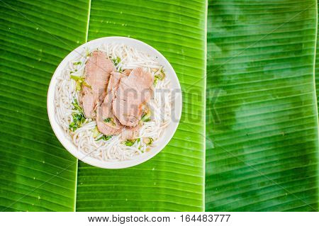A Bowl Of Traditional Vietnamese Beef Soup Pho Bo On Banana Leaf Background.