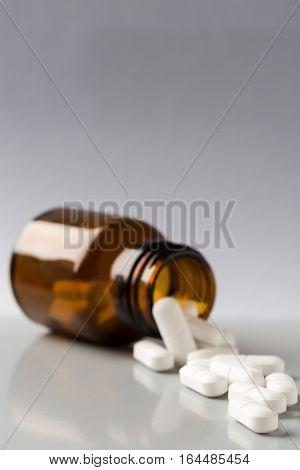 Glass bottle of white pills on gray background