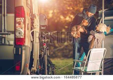 Family with Dog on a Campground with Camper Van. Father Playing with Dog and His Daughter. Caucasian Family Recreation Time.