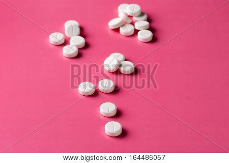 Heap of round white pills on pink background