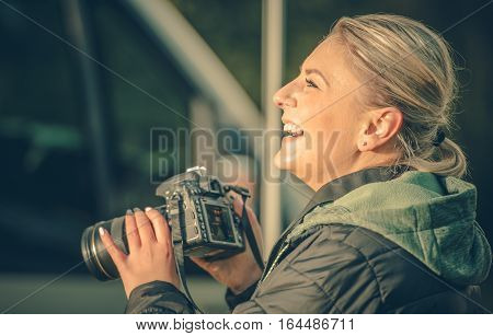 Happy Female Photographer. Smiling Caucasian Woman with Professional Digital Camera in Hands. Photography Hobby.