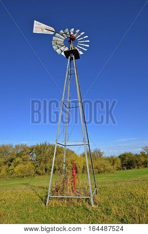 An old water tower and wind wane stands tall in a pasture over a well with a handle pump