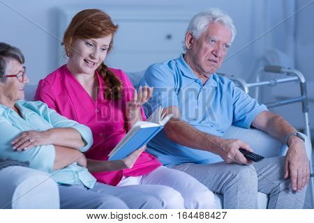 Caregiver Reading Book To Patients
