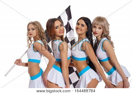 Sexy long haired girls in formula one style white and blue tops and mini skirts and high heel shoes posing with black and white flag in studio.