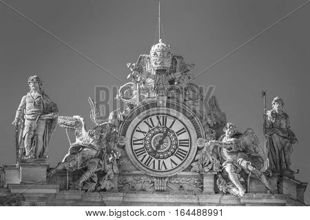 ROME, ITALY - January 24, 2016: Statues and clock on the roof of the basilica of San Pietro in Vatican City in Rome. Italy. Black and white