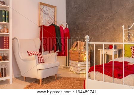 Functional light room with clothes rack armchair bed and bookcase