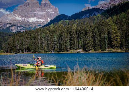 Scenic Mountain Lake Kayak Tour. Caucasian Men in the Kayak.