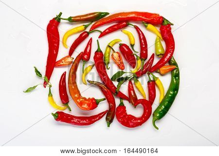 Plenty of green, yellow and red chili pepper isolated on white background. Closeup pile of ideal hot spicy vegetables, healthy natural organic food, top view