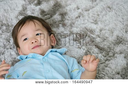 Closeup cute asian kid lied on floor in happy emotion with smile face on gray carpet textured background